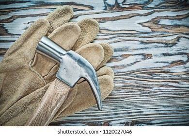 Leather protective gloves claw hammer on wooden board.