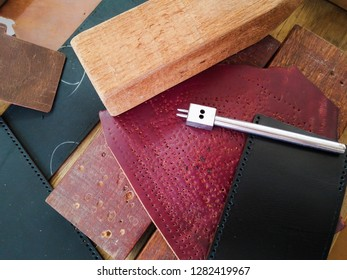 Leather punching tools and materials that are hole puncher, wooden hammer, wood poundo board and pieces of leather