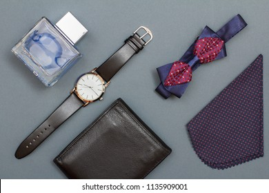 Leather purse, watch with a black leather strap, cologne for men, bow tie and handkerchief on grey background. Accessories for men. Top view