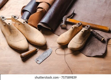 Leather in rolls, cobbler tools and shoe lasts in a workshop. Leather craft tools.