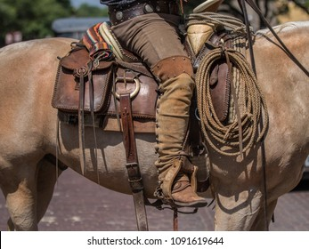 Leather saddle bag, boots, reins, rope Cowboy in saddle