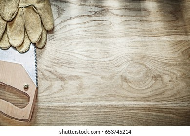 Leather safety gloves sharp handsaw on wooden board copy space construction concept.