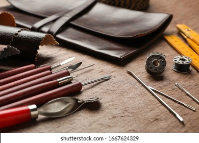Leather samples and tools on brown table, closeup