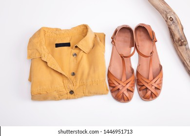 Leather sandals and yellow blouse on white background. Woman casual flat sole summer shoes