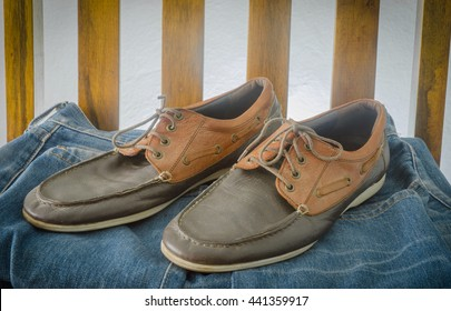 leather Shoes and blue jean on wooden chair.