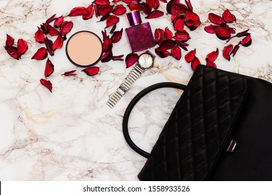 leather shoulder bag, bottle perfume and foundation, hand watch on marble background