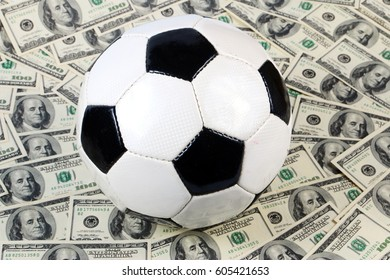 Leather soccer ball on the field of background paper dollar bills