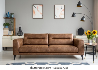 Leather sofa next to table with sunflowers in grey living room interior with posters. Real photo