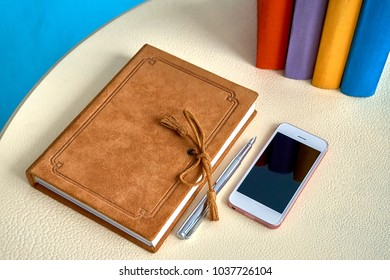 Leather suede paper dairy orange notebook with calligraphy pen and smartphone on the table