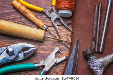 Leather and tools on wooden background