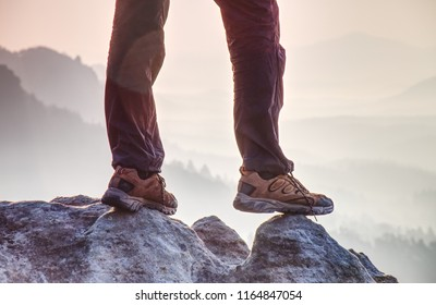 Leather trekking shoes on peak of rock above misty valley. Free way traveller