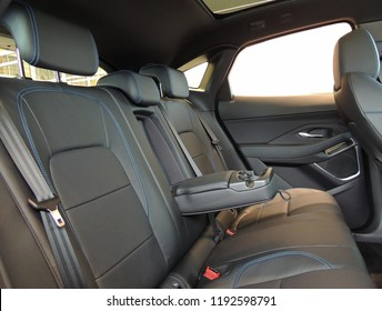 Leather trimmed folding armrest with cup holders in rear seats inside a vehicle