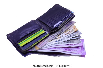 Leather wallet with bank cards and Indian currency note inside on the white table.