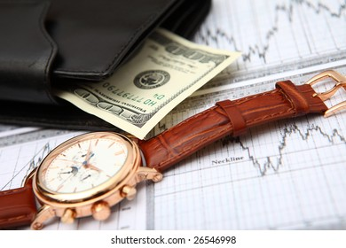 leather wallet cash & gold clock on business graph