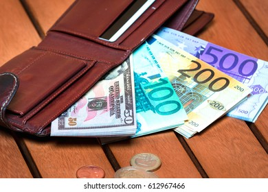 Leather wallet full of cash on a wooden table, dollars, euros