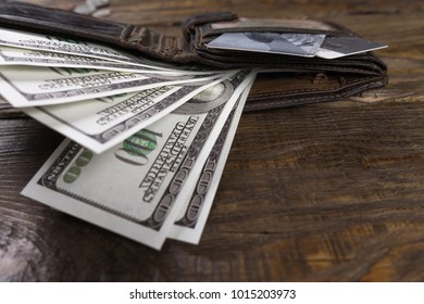 Leather wallet with hundreds and credit cards lying on a wooden table. Copy paste