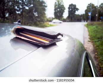 Leather Wallet with money and credit cards on the car  vehicle roof. Lost or forgotten wallet on city street. loss concept. Real people. Copy space.