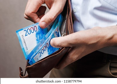 Leather wallet with money in male hands. Russian money, russian cash background.