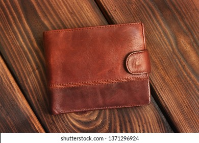 Leather wallet on a wooden background.