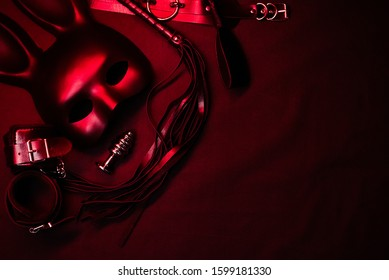 Leather whip, handcuffs, choker, mask and metal anal plug for BDSM sex with submission and domination with copy space on black and red dark background
