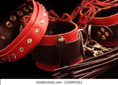 Leather whip, red leather handcuffs, red mask on a black background