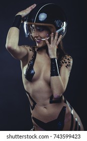 Leather, woman with motorcycle helmet, naked girl dressed with black ribbons by the body. concept speed and security