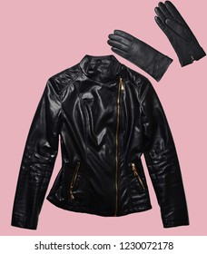 Leather woman's jacket and gloves isolated on pink background. Minimalism, fashionable clothes and accessories