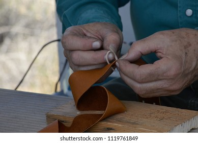 Leather worker adds detail to strap