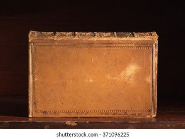 Leatherbound book with blank cover on a wooden desk standing  on edge