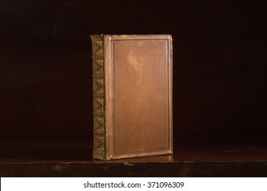Leatherbound book with blank cover standing on a wooden desk