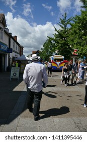 Leatherhead, High Street, Surrey, UK - May 27 2019: The Rear View of a Man Wearing a Trilby Hat Walking Towards an Ice Cream Van on a Warm Summers Day, with Oncoming People Strolling Past the Shops.