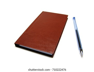 Leather-like brown small agenda and blue ball pen without cap isolated on a seamless white background.