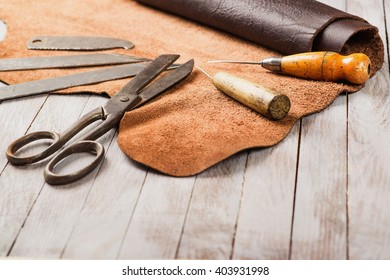 Leathersmith work desk . Pieces of hide and leather working tools on a work table.