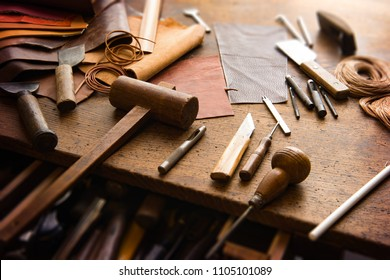 Leathersmith's work desk . Pieces of red, orange, yellow, green, tan and brown hide and leather working tools on a work table.