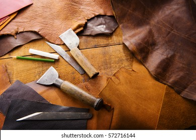 Leathersmith's work desk . Pieces of tan and brown hide and leather working tools on a work table.