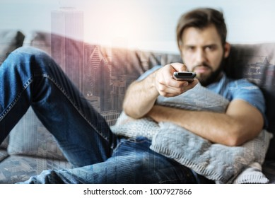 Leave me alone. Angry disappointed unshaken man looking lying on the sofa straight and holding the console.