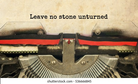 Leave no stone unturned typed words on a vintage typewriter with vintage background