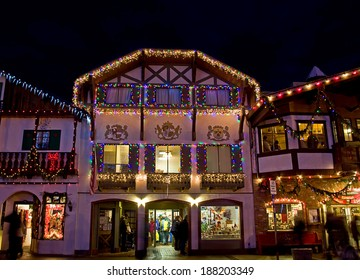 LEAVENWORTH, WA/USA - DECEMBER 21, 2013: This illustrative editorial a Bavarian store lit up with Christmas lights at night with shoppers.