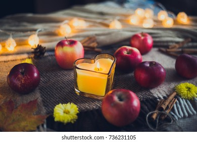 leaves, apples and a burning candle and lights