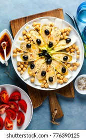 The leaves of Belgian endive with hummus, chickpeas and black olives. With strong olive oil of red pepperoncino and fresh cut tomatoes . Modern delicious food for vegetarians and gourmets.