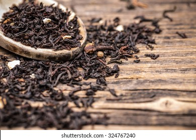 Leaves of black tea in wooden spoon
