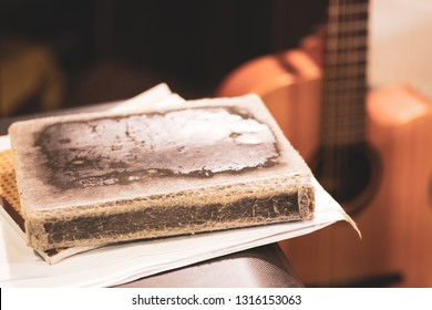 the leaves and the book in the old cover on the background guitar, guitar out-of-focus light toning