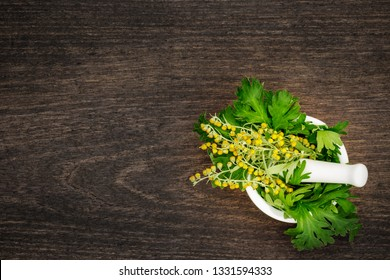 The leaves and flowers of wormwood in mortar bowl on wooden table, top view. Artemisia absinthium ( absinthe, absinthium, absinthe wormwood, wormwood ) plant, close up