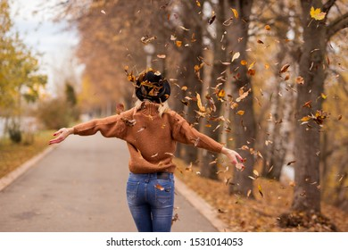 leaves in focus. beautiful young cheerful blonde girl in a brown warm sweater, black felt hat, blue jeans throws up autumn leaves in the park. horizontal photo. back view.