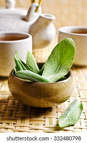 Leaves of fresh sage on a background of ceramic cups with tea