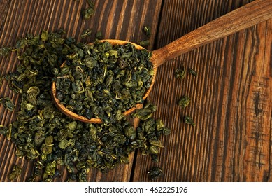 leaves of green tea in a wooden spoon on vintage table