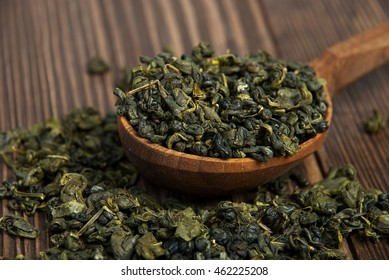 leaves of green tea in a wooden spoon on vintage wooden table