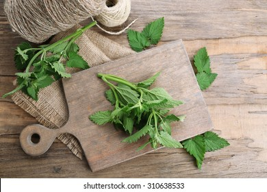 Leaves of lemon balm with rope on wooden table, top view