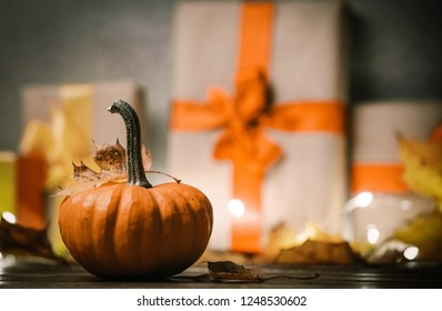 leaves and pumpkin with Halloween gift box on Fairy Ligths background. Autumn season image composition
