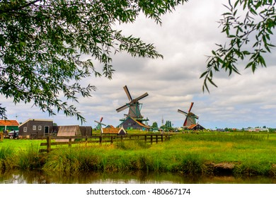 Leaves from trees surrounding view of old windmills with large bases at farm under partly cloudy skies